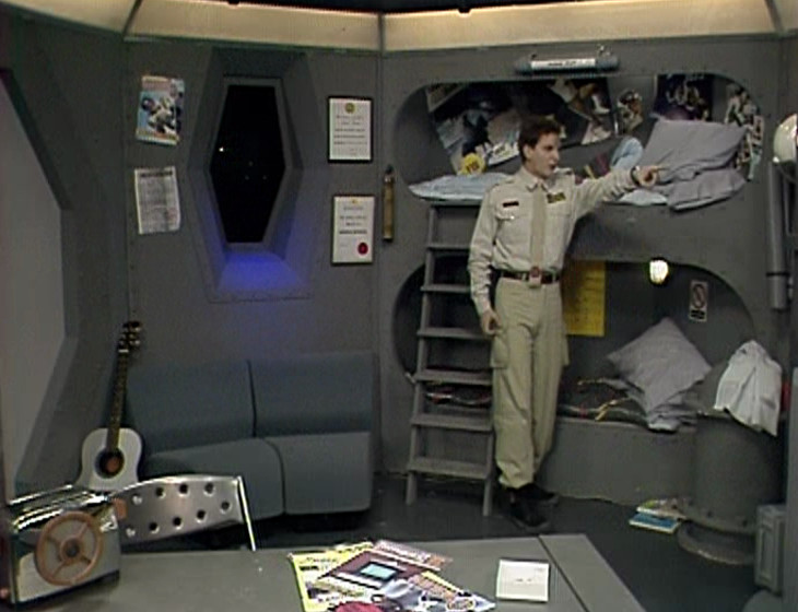 Rimmer pointing at Holly on the monitor