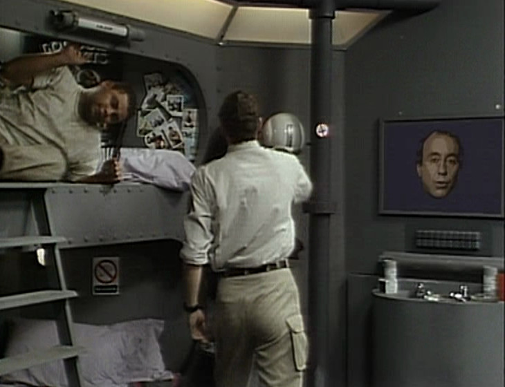 Rimmer and Lister in the bunkroom with Holly on the monitor