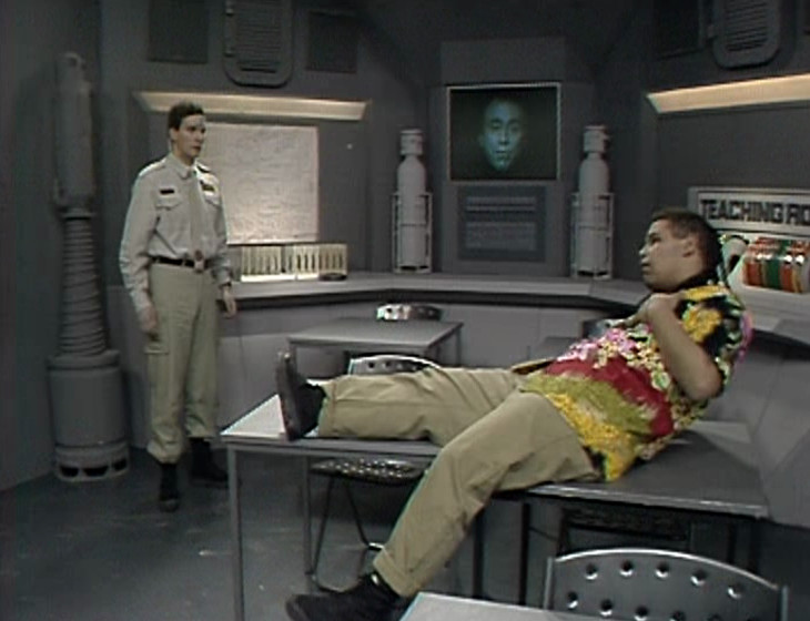 Rimmer and Lister puzzled in the Teaching Room learning about Cat, with Holly in vision