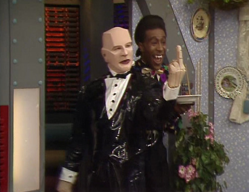 Kryten does a naughty and sticks his finger up like a rude robot
